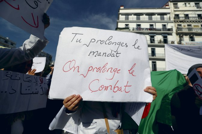 "A demonstrator carries a sign as teachers and students take part in a protest demanding immediate political change in Algiers, Algeria March 13, 2019. The sign reads: ""You extend your term, we extend our combat"". REUTERS/Zohra Bensemra"